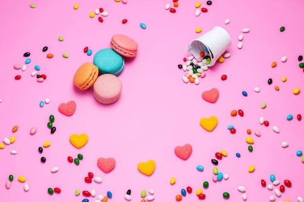 Eine draufsicht macarons und marmelade bunte französische kuchen zusammen mit mehrfarbigen bonbons auf dem rosa hintergrund süße süßigkeiten Kostenlose Fotos