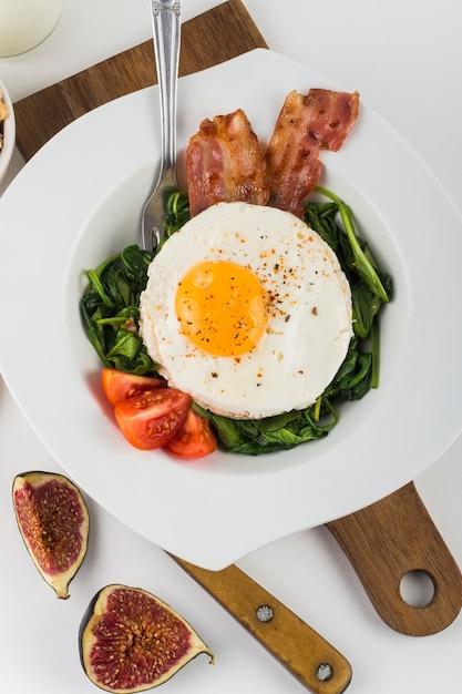 Eine draufsicht von ei mit speck; feige; spinat und tomate auf weißem teller vor weißem hintergrund Kostenlose Fotos