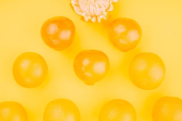 Eine draufsicht von ganzen orangen auf gelbem hintergrund Kostenlose Fotos