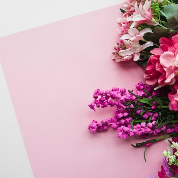 Eine draufsicht von gefälschten blumen auf rosa hintergrund Kostenlose Fotos