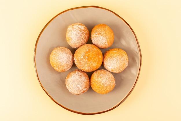 Eine draufsicht zuckerpulverkuchen runde süße gebackene köstliche kleine kuchen innerhalb runder plattform und sahnehintergrundbäckerei süßer keks Kostenlose Fotos