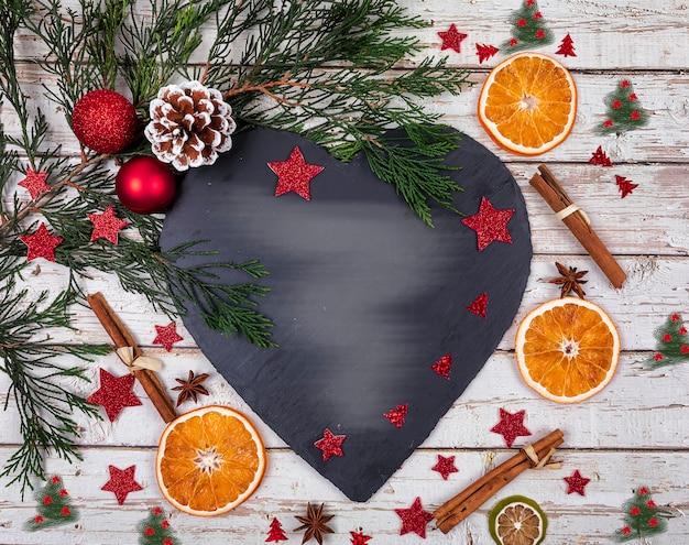 Eine dunkle käseservierplatte mit kopienraum für text im weihnachtsdekor mit weihnachtsbaum, trockene orange über alter tabelle Premium Fotos