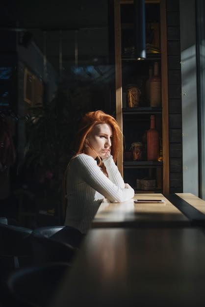 Eine einsame junge frau, die nahe dem fenster mit handy auf tabelle sitzt Kostenlose Fotos