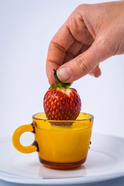 Eine erdbeere in einer milchschale durch eine frauenhand auf weiß Premium Fotos