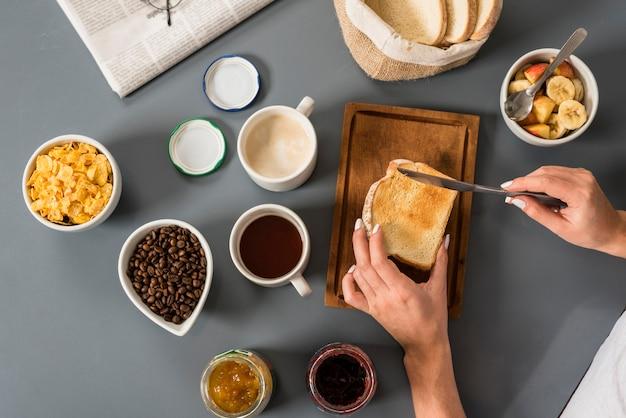 Eine erhöhte ansicht der hand der frau, die frühstückt Kostenlose Fotos