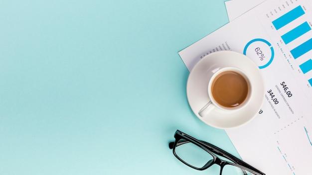 Eine erhöhte ansicht der kaffeetasse auf geschäftsbudgetplan und -brillen auf blauem hintergrund Kostenlose Fotos