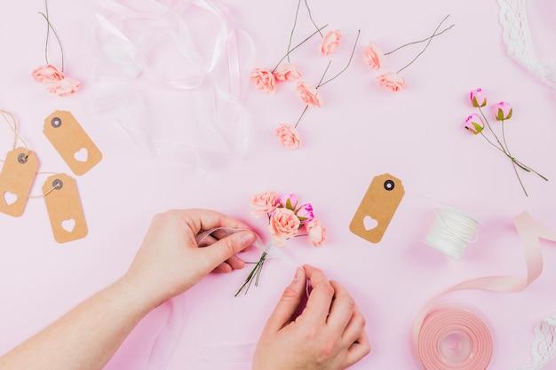 Eine erhöhte ansicht der menschlichen hand die künstlichen blumen mit band auf rosa hintergrund bindend Kostenlose Fotos