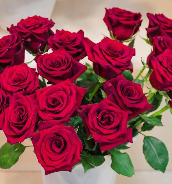 Eine erhöhte ansicht der rotrosenblume im vase Kostenlose Fotos