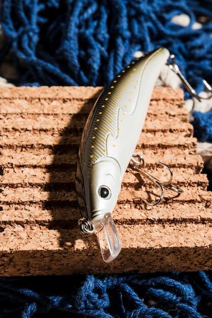 Eine erhöhte ansicht des fischereiköders mit haken auf korkenbrett über dem blauen fischernetz Kostenlose Fotos