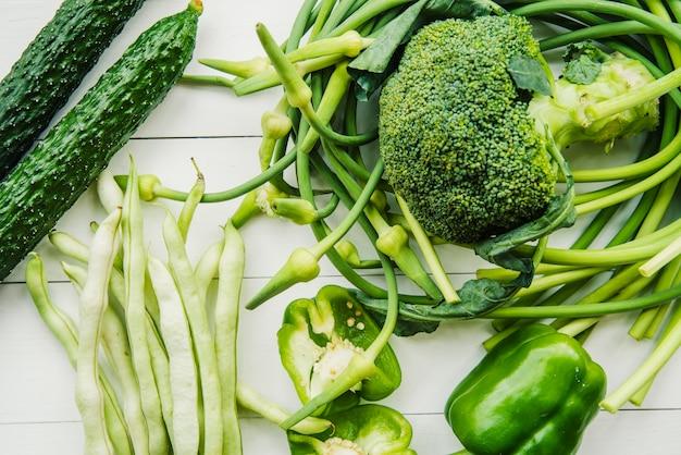 Eine erhöhte ansicht des gesunden grünen gemüses auf die tischplatte Kostenlose Fotos
