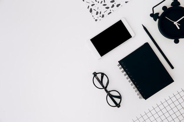 Eine erhöhte ansicht des weckers; handy; tagebuch; bleistiftpapier und brillen auf weißem hintergrund Kostenlose Fotos
