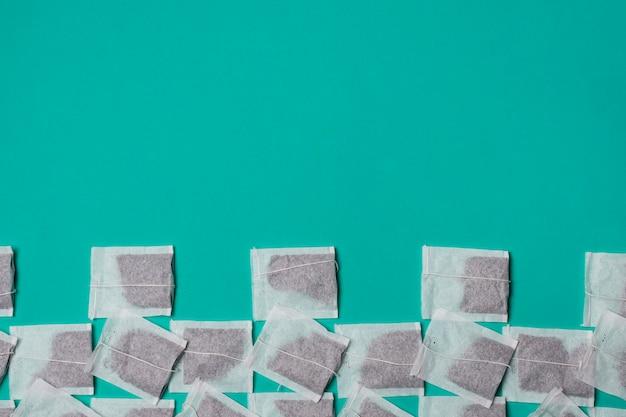 Eine erhöhte ansicht des weißen teebeutels auf grünem hintergrund Kostenlose Fotos