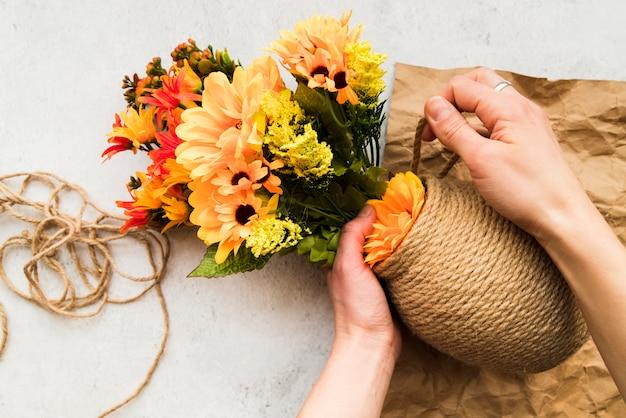 Eine erhöhte ansicht einer frau, die die vase mit schnur macht Kostenlose Fotos