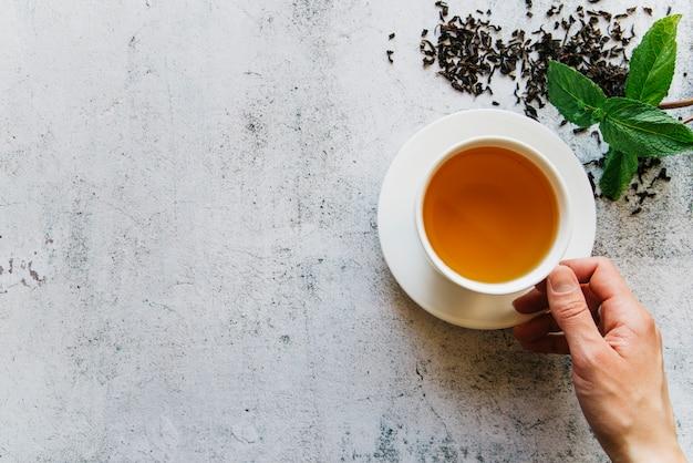 Eine erhöhte ansicht einer person, die tasse tee mit getrockneten teeblättern und minze hält Kostenlose Fotos