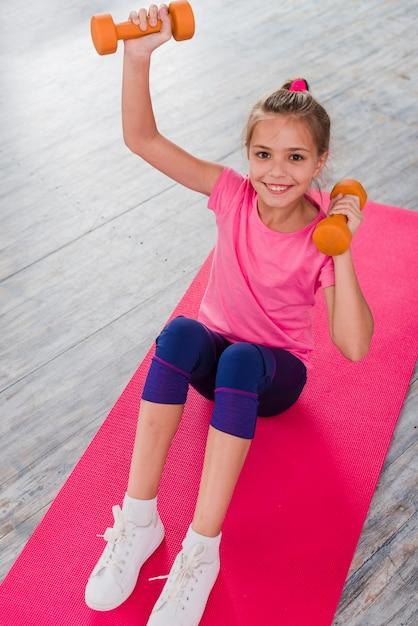 Eine erhöhte ansicht eines blonden mädchens, das auf dem rosa teppich trainiert mit dummkopf sitzt Kostenlose Fotos