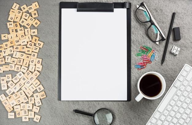 Eine erhöhte ansicht von buchstabenholzblöcken mit büroartikel auf grauem schreibtisch Kostenlose Fotos