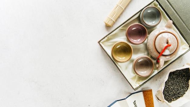 Eine erhöhte ansicht von chinesischen keramischen teetassen und von teekanne mit trockenen teeblättern auf konkretem hintergrund Kostenlose Fotos