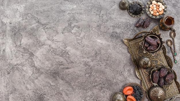 Eine erhöhte ansicht von datumsangaben; nüsse und rosinen auf metallischem behälter über dem grauen konkreten hintergrund Kostenlose Fotos