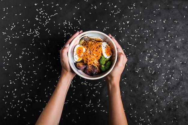 Eine erhöhte ansicht von den händen, die schüsseln ramennudeln mit eiern und salat halten, verbreitete mit reiskörnern auf schwarzem hintergrund Kostenlose Fotos