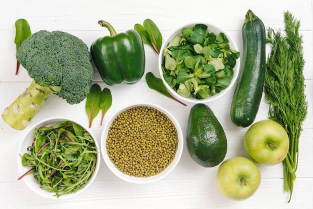 Eine erhöhte ansicht von gesundem frischem gemüse; mungobohnen und apfel auf weißer tabelle Kostenlose Fotos