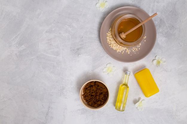 Eine erhöhte ansicht von honig; gelbe seife; ätherisches öl flasche; kaffeepulver mit weißen blumen auf konkretem hintergrund Kostenlose Fotos