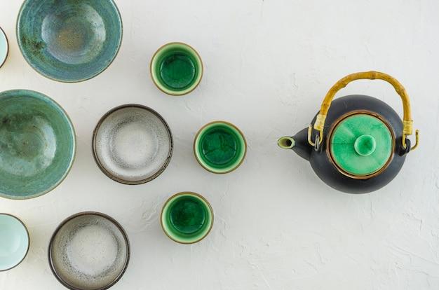 Eine erhöhte ansicht von leeren teeschalen mit der teekanne lokalisiert auf weißem hintergrund Kostenlose Fotos