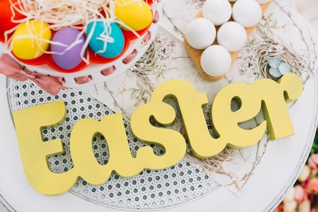 Eine erhöhte ansicht von ostern-text mit dekorativen bunten ostereiern auf weißer tabelle Kostenlose Fotos