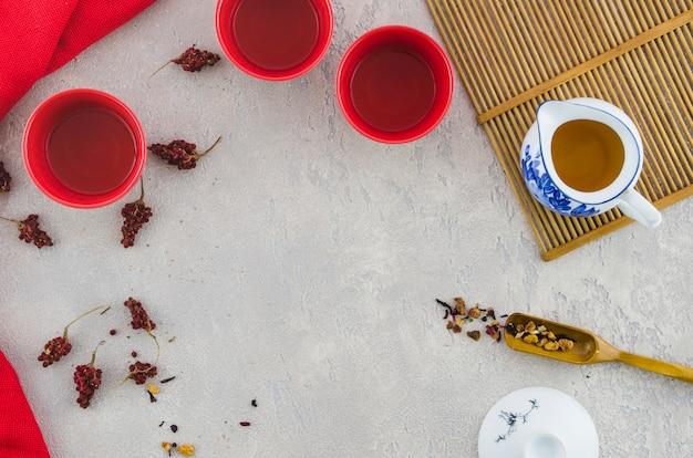 Eine erhöhte ansicht von roten keramischen schalen und von kräutertee im pitcher auf strukturiertem hintergrund Kostenlose Fotos