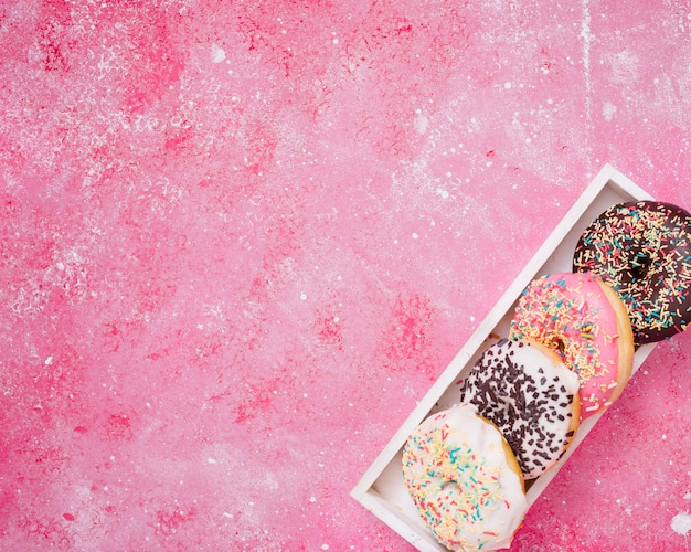 Eine erhöhte ansicht von schaumgummiringen in der weißen holzkiste an der ecke des rosa hintergrundes Kostenlose Fotos