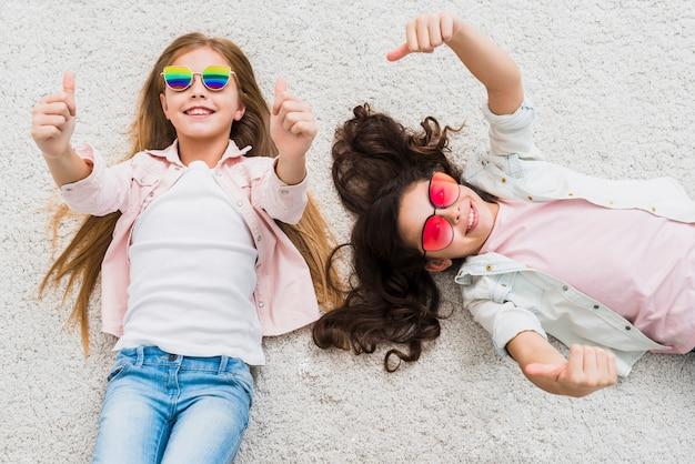 Eine erhöhte ansicht von zwei freundinnen, die auf dem teppich zeigt daumen herauf zeichen liegen Kostenlose Fotos