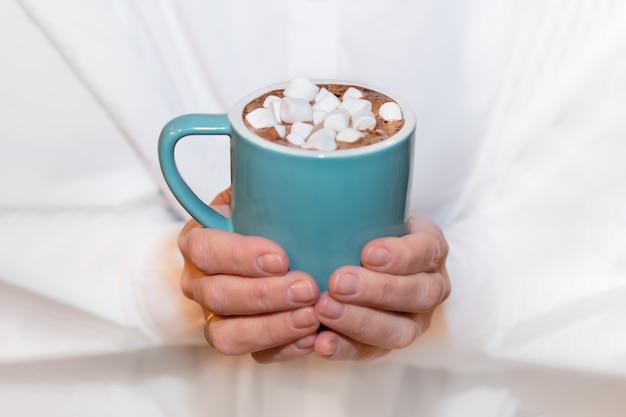 Eine erwachsene frau in einem weißen hemd hält eine blaue tasse kakao mit marshmallows in den händen. Premium Fotos