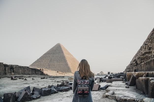Eine europäische blondine geht in der nähe der pyramiden in der wüste in kairo spazieren. die frau gegen die alten gebäude in gizeh. Premium Fotos