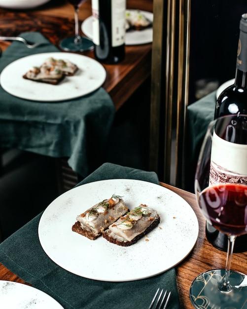 Eine fischmahlzeit der draufsicht innerhalb des weißen tellers zusammen mit rotwein auf dem tischnahrungsmittel-restaurant Kostenlose Fotos