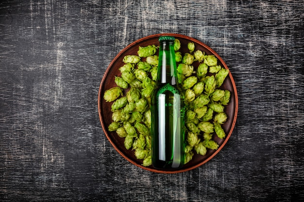 Eine flasche bier auf einem grünen frischen hopfen in einer platte vor dem hintergrund einer schwarzen verkratzten tafel Premium Fotos