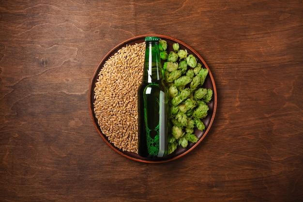 Eine flasche bier auf einem grünen frischen hopfen- und weizenkorn in einer platte gegen das hölzerne braune brett Premium Fotos