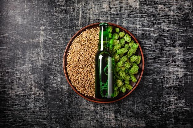 Eine flasche bier auf einem grünen frischen hopfen- und weizenkorn in einer platte gegen den hintergrund Premium Fotos