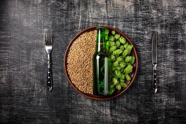 Eine flasche bier auf einem grünen frischen hopfen- und weizenkorn in einer platte vor dem hintergrund einer schwarzen verkratzten tafel Premium Fotos