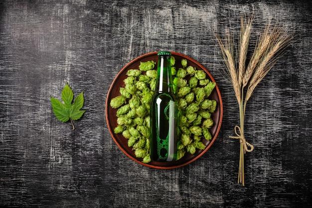 Eine flasche bier auf einem grünen hopfen in einer platte mit den ährchen und hopfenblatt des weizens vor dem hintergrund eines schwarzen verkratzte kreidebrett Premium Fotos