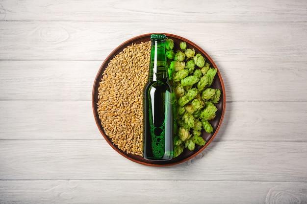 Eine flasche bier auf einer platte mit grünen hopfen und haferkorn auf einem weißen hölzernen brett Premium Fotos
