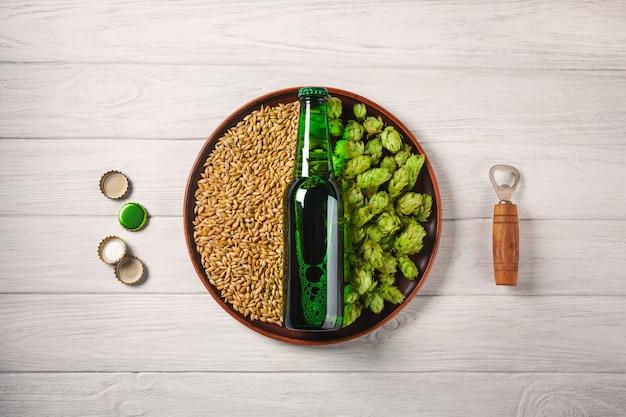 Eine flasche bier auf einer platte mit grünen hopfen und haferkorn mit öffner und corcks auf einem weißen holzbrett Premium Fotos