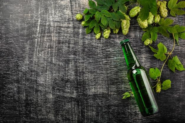 Eine flasche bier mit einem bündel frischen grünen hopfen auf einem schwarzen zerkratzten kreidebrett Premium Fotos