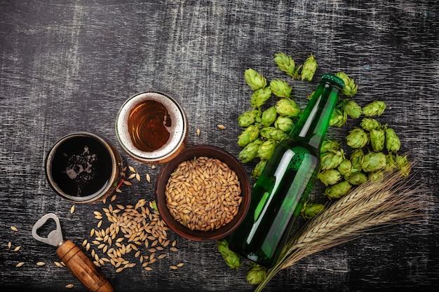 Eine flasche bier mit grünem hopfen, hafer, weizenährchen, öffner und gläsern mit dunklem und hellem bier auf schwarz zerkratzter kreidetafel Premium Fotos