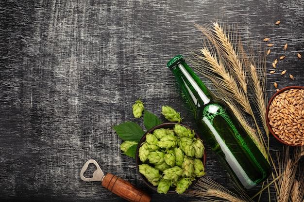 Eine flasche bier mit grünen hopfen, ährchen, schalenhafer und öffner auf einem schwarzen zerkratzten kreidebrett Premium Fotos