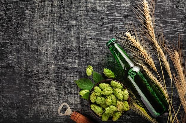 Eine flasche bier mit grünen hopfen, ährchen und öffner auf einem schwarzen zerkratzten kreidebrett Premium Fotos