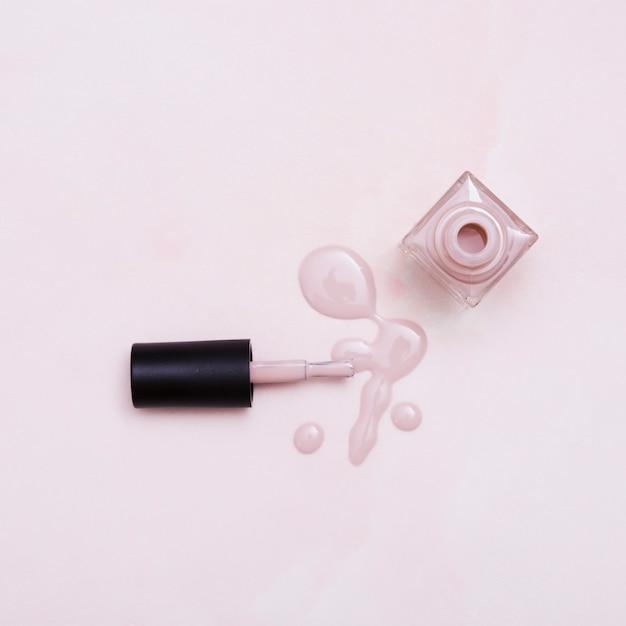 Eine flasche rosafarbener nagellack heraus verschüttet auf farbigem hintergrund Kostenlose Fotos