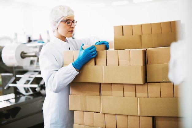 Eine fokussierte arbeitnehmerin in steriler kleidung zählt die kisten, die zur auslieferung bereit sind. Premium Fotos