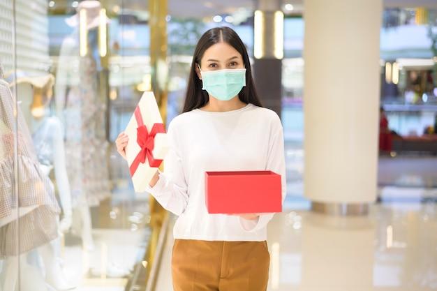 Eine frau, die eine schutzmaske trägt, die eine geschenkbox im einkaufszentrum hält und unter covid-19-pandemie, erntedankfest und weihnachtskonzept einkauft. Premium Fotos