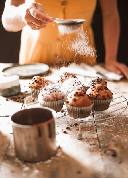 Eine frau, die zucker auf selbst gemachten muffins auf abkühlendem gestell staubwischt Kostenlose Fotos