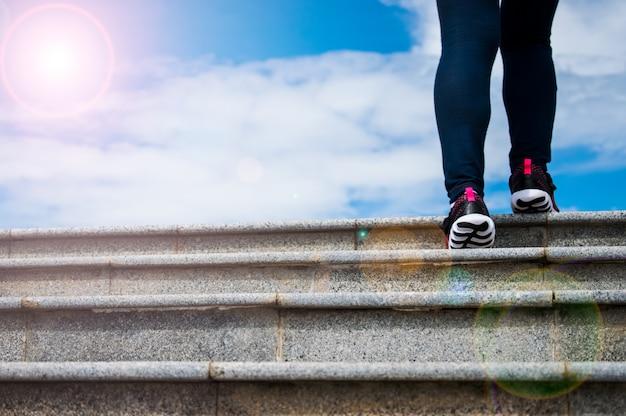 Eine frau geht bis zur spitze der treppe mit hintergrund des blauen himmels. Premium Fotos