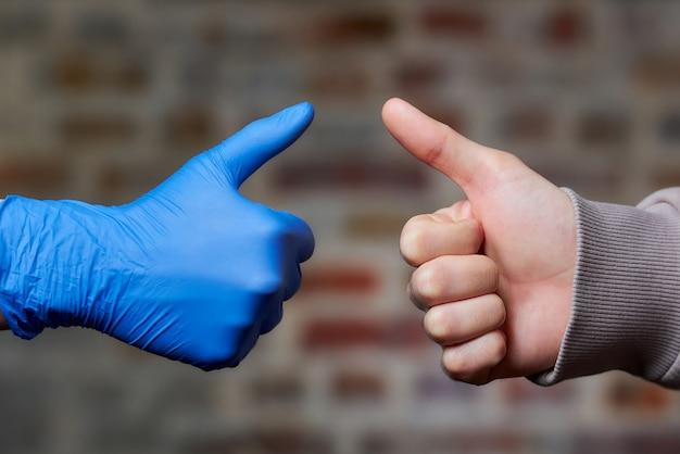 Eine frau greift mit einem einweghandschuh zu einem mann, der auch ihre daumen mit nackter hand aufgibt. Premium Fotos